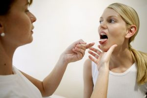 Doctor examining female patient with tongue depressor